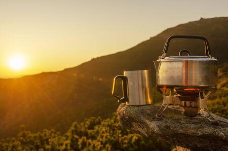 屋外で朝のホットドリンク。山の高い岩の上に立っているティーポット、マグカップ、キャンプストーブ。ストーブとティーポットに焦点を当てます。 写真素材