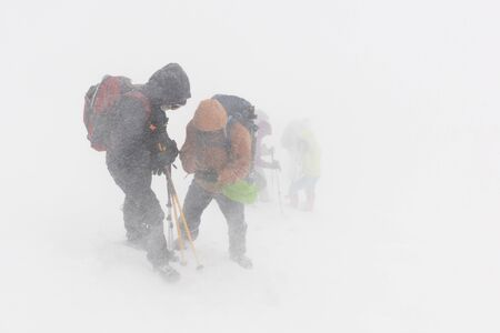 Group of hikers in the mountains trying to navigate the terrain in extreme bad weather conditions