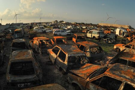Car cemetry. Dump of old rusted cars. Metal recycling. Waste of energy