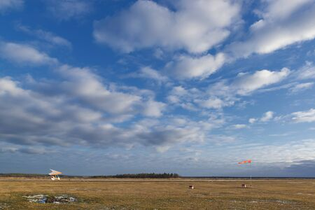 Airfield with a small plane and windsock. Flying adventure Banco de Imagens