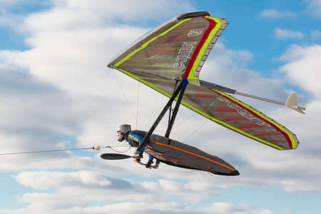 2020-02-09 Byshiv, Ukraine. Hang glider pilot fly on his bright colored wing with bright blue sky on the background.