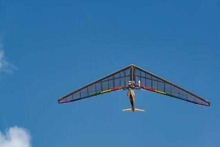 Bright rainbow colored hang glider wing in flight. Mankind dream of flight come true.