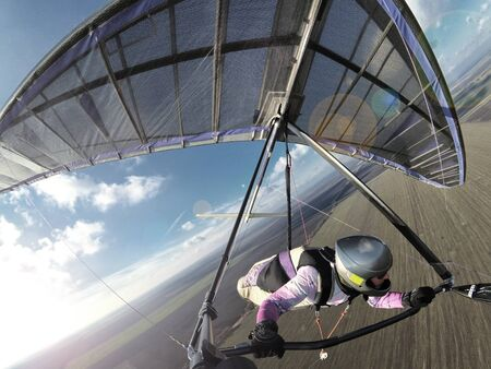 Hang glider pilot fly like a bird above ground. Extreme sport. Imagens