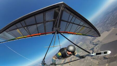 Hang glider pilot with his colorful wing flies alone far from other people. Concept of self isolation and social distance in the wild nature.