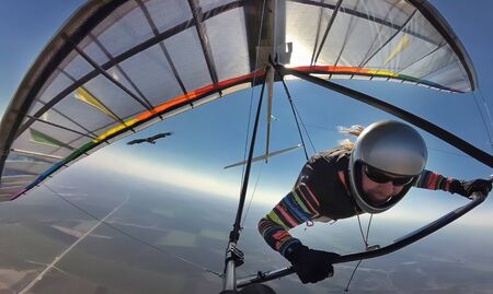 Hang glider pilot on colorful wing flies together with eagle. Dream to fly like a bird come true. Social distancing in the wild nature far from other people.