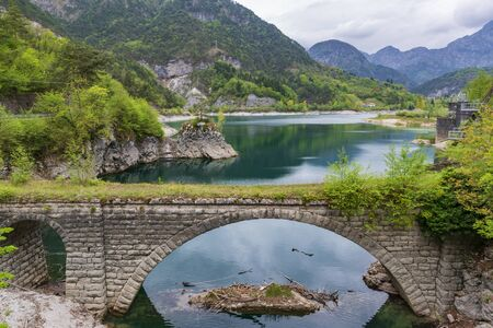 Stone arch bridge and mountain lake in Northern Italy near Meduno Archivio Fotografico