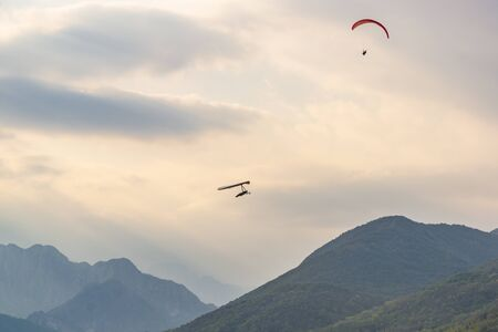 Hang glider and paraglider fly near Meduno in Pordenone, Italy