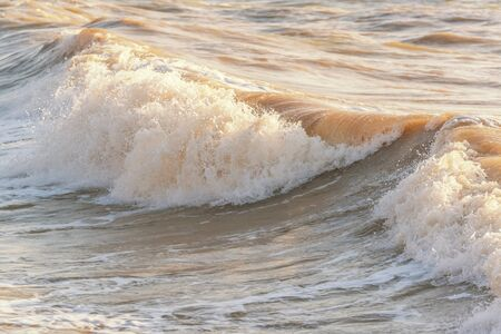 Rolling waves at the seaside. Sea waves illuminated by sun