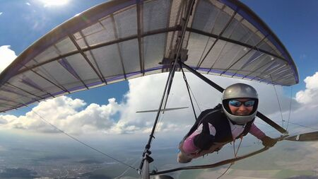 High five in the sky. Girl pilot on a hang glider on high altitude