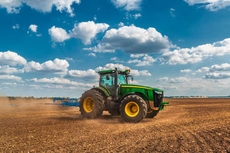Big tractor on the cultivated field. Agricultural industry. Soil preparation