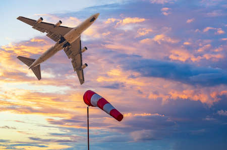 Windsock and jet plane in the bright sunset sky. Weather at the airport concept