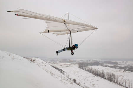 Student hang glider pilot on the training hill. Hang glider wing silhouette