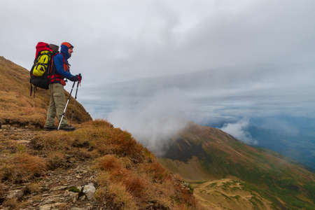 Hiker with backpack and other gear on the mauntain top. Vacation in the mountains.
