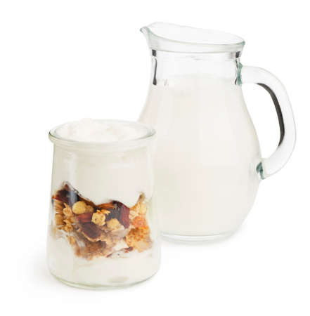 healthy layered yogurt with granola and fruits with milk jar on white background