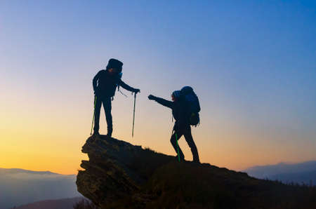 Helping hand on the top. Hiker with backpack helps other hiker to reach the summit. Concept of help, achievement and friendship. 版權商用圖片