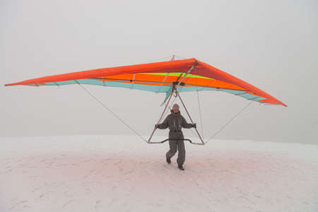Girl run on snow with colorful hang glider wing. Winter sport activity.