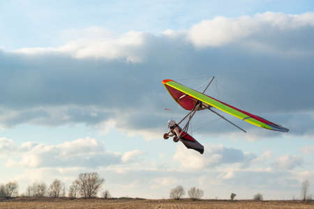 Brave girl learn to fly on the colorful hang glider wing. Extreme sport activity with beautiful sunset sky on the background. Mastering hang gliding Banque d'images