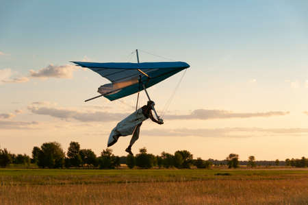 Learning to fly on a hang glider. Pilot prepares to land with his wing. Hang glider wing silhouette