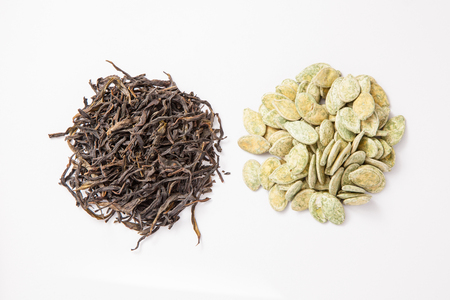 Chinese traditional dry tea and pumpkin seeds on white background