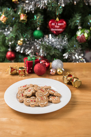 galleta de jengibre: The white plate of the gingerbread man on the wooden table and Christmas decorations