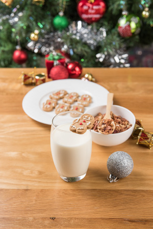 christmas cracker: a plate of gingerbread man onthe wooden table and Christmas decorations Stock Photo