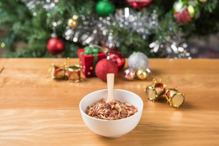 christmas cracker: The cereal in the white bowl is on the wooden table and Christmas decorations. Stock Photo