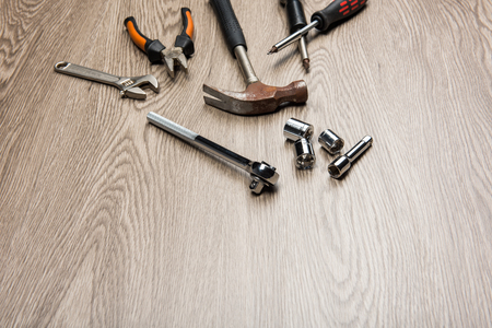 The repair tools is placed on the wooden table.