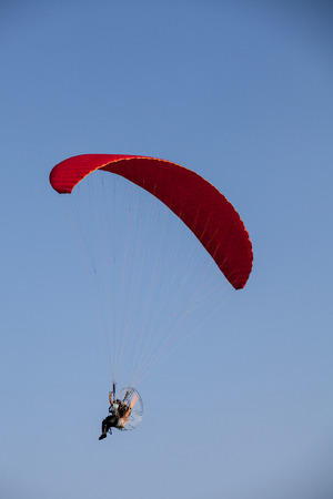 paramotor flying on blue sky