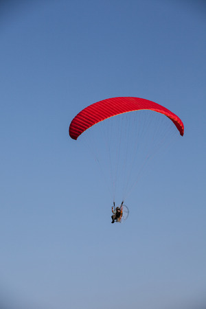paramotor flying on blue sky Stock Photo - 66790301