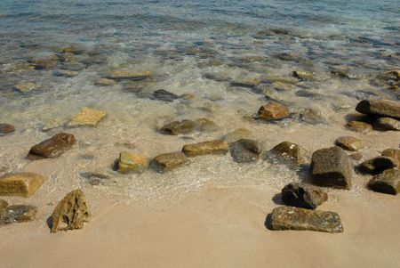 Rocks on a sandy beach on Pacific bay.