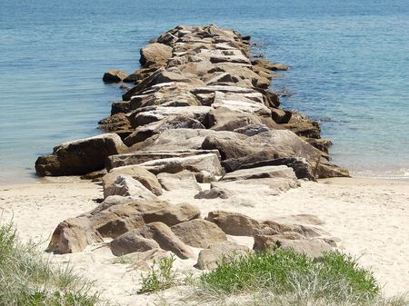 Breakwater on a blue Pacific beach. Stock Photo
