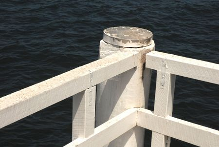 White wharf railings contrasted by dark blue water. Stock Photo