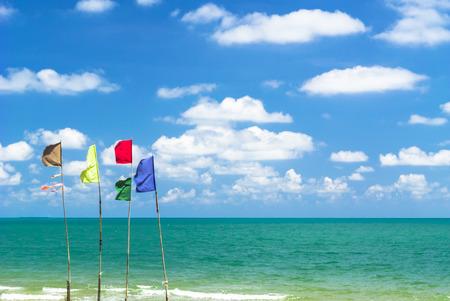 multi colour: Banderas del multicolor en la playa, cielo azul de fondo Foto de archivo