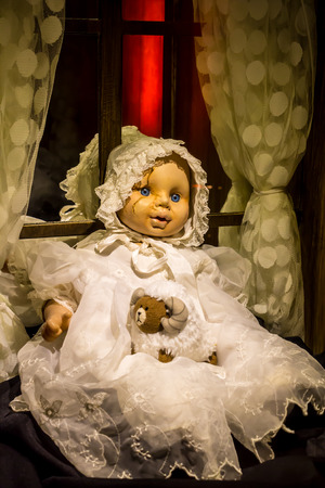 A scary old, broken doll against a window. photo
