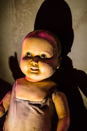 A scary old, broken doll against a damaged wall. photo