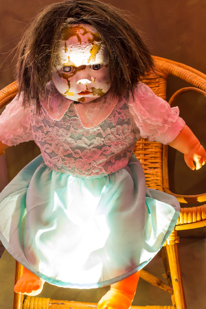 A scary old, broken doll sitting in basket. photo