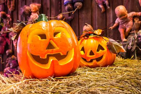 Jack o lanterns Halloween pumpkin face on scary dools background. Фото со стока