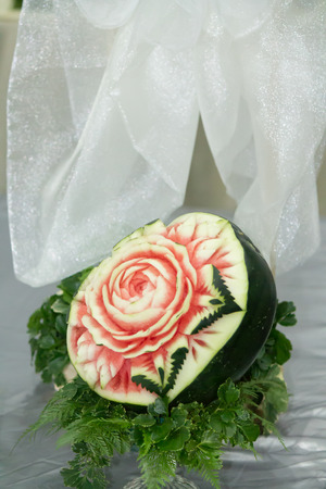 culinary skills: Watermelon carving in the form of flower, fern leaves on table set.