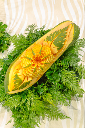 cuisine entertainment: Papaya fruit carving in the form of flower and fern leaves on white isolated. Stock Photo
