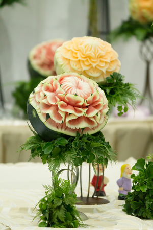 cuisine entertainment: Watermelon and cantaloupe  fruit carving  on table sets. Stock Photo
