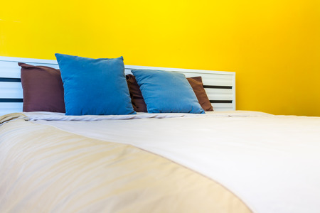 pillow case: Ready for bed, White bed linens and refreshing colorful wallpaper in simple bedroom.