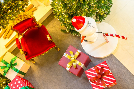 indoor background: Ready for CHristmas,  Adorned Christmas Tree , Chair ,  Fireplace, Snowman, Gift  inside Living space with copyspace.