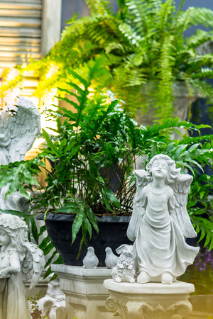 Statue Cupid and waterfall in cozy garden on summer.