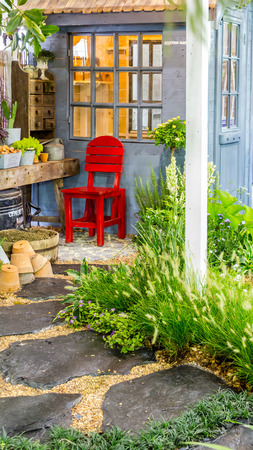 Relaxing area with red chair in cozy garden on summer.