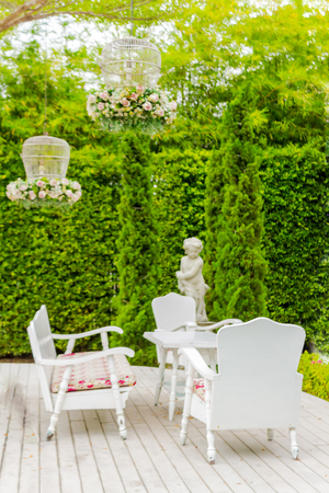 Chair and statue of Cupid in cozy garden on summer.