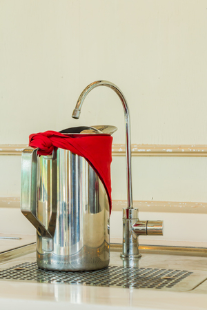 Stainless steel jug of cold water and Faucet filter on table in domestic Kitchen. Stock Photo