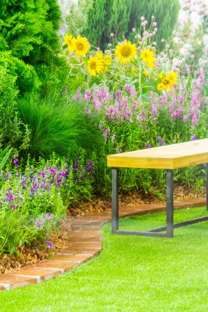Wood couch in flower cozy garden. Stock Photo