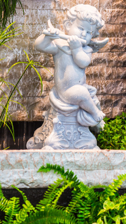 Statue Cupid and waterfall in cozy garden.