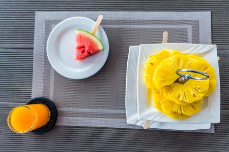 Flatlay slide fruit, pineapple, watermelon decoration in tier with orange juice on table for breakfast.