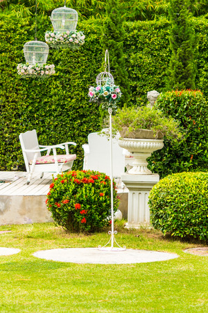 White tableset and flower pot on relaxing space in cozy garden on summer.